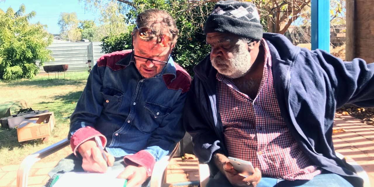 Sammy Butcher composing and dictating lyrics in the Luritja language to Neil Murray who is writing them down - 19/6/2018, Alice Springs
